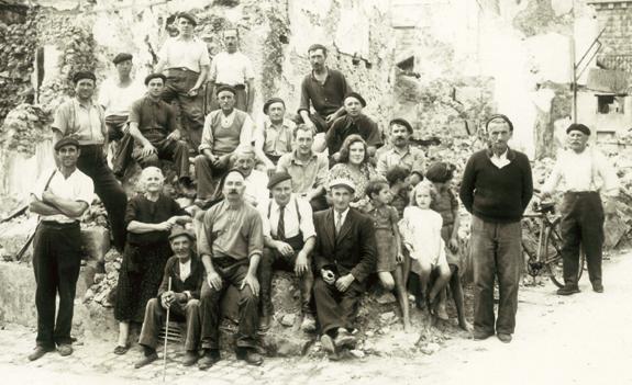 Groupe d'habitants posant dans les ruines de leur village, à Mouleydier.