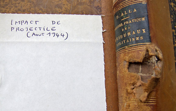 Impact de projectile sur le dos d'un livre de la Bibliothèque de l'École militaire de Paris.