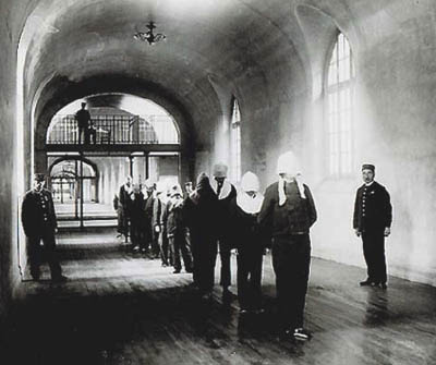 Détenus portant le capuchon belge avançant dans un couloir de la prison de Fresnes
