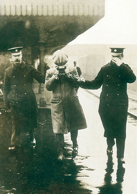 Arrestation d'un inculpé, visage masqué, sur le quai d'une gare en Grand-Bretagne