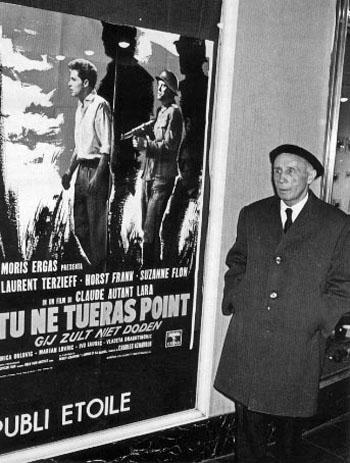 """Le pacifiste et libertaire Louis Lecoin photographié devant l'affiche du film de Claude Autant-Lara, """"Tu ne tueras point""""."""