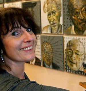 Francine Mayran devant le mur de la survivance, galerie de portraits de déportés dans les camps nazis.