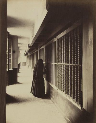Religieuse, galerie de cellules à 1 lit (dite Ménagerie), prison Saint-Lazare, faubourg Saint-Denis, Paris Xe, juin 1888. Photographie de Pierre Emonts, © Musée Carnavalet/Roger-Viollet.