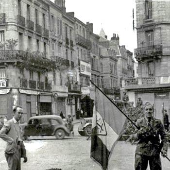 Une image de l'occupation à Périgueux, devant le siège du SD (Sicherheitsdienst, service de sécurité) avec un membre de ce qu'on appelle la Gestapo, exhibant sur les boulevards un drapeau pris au maquis le 22 juin 1944, lors de l'attaque du château de la Feuillade. © Photo collection DCJM / Patrice Rolli.