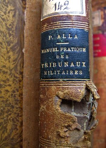 Dos d'un livre de la Bibliothèque de l'École militaire de Paris portant la trace d'un projectile, souvenir du 25 août 1944